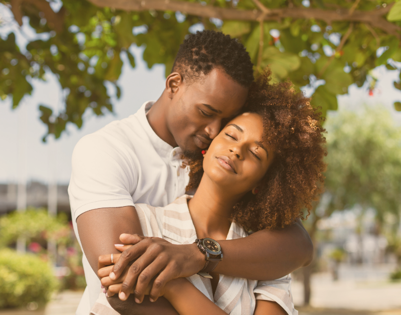 man and woman hugging and smiling outside