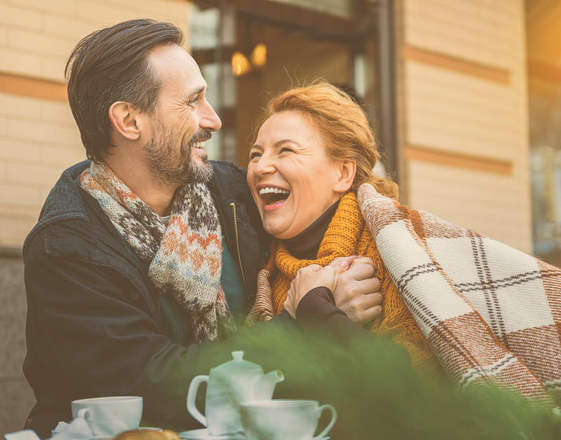 older couple laughing and snuggling together outside in cold weather