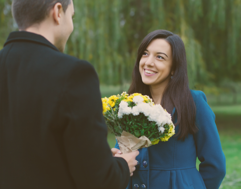man handing flowers to smiling woman outside