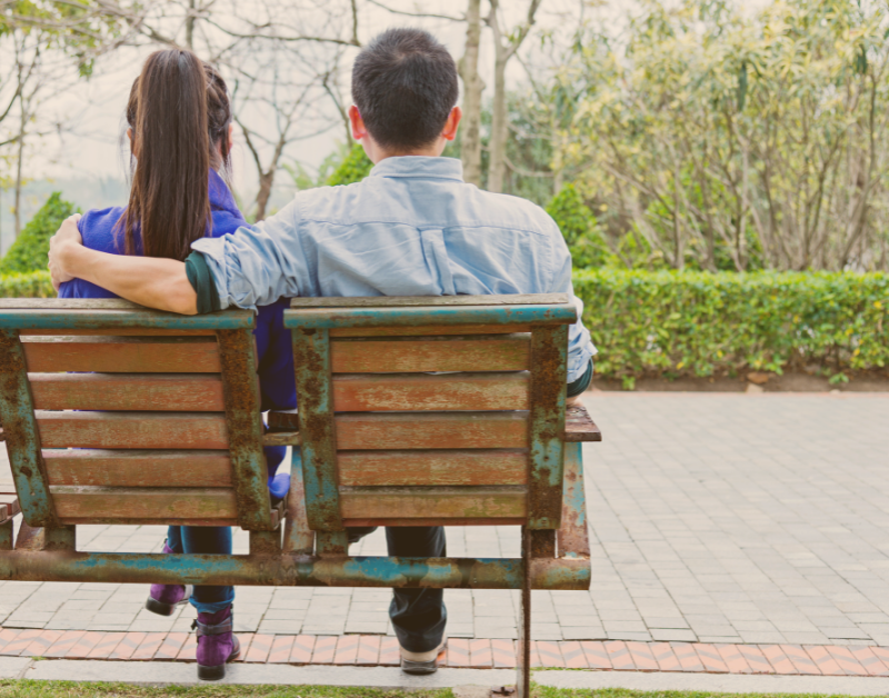 man and woman sitting on bench together