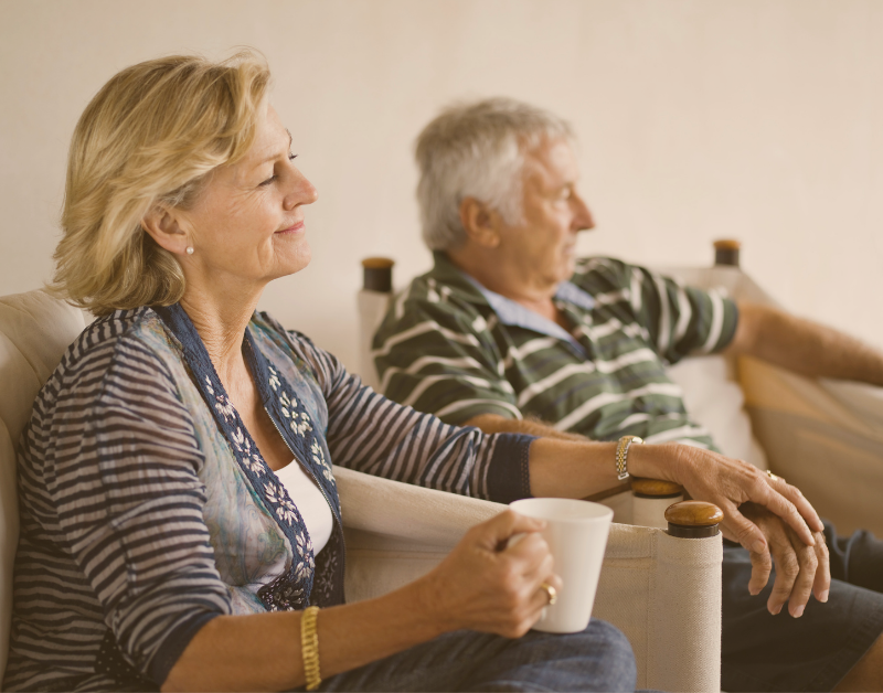older man and woman sitting holding hands