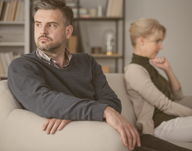 man and woman sitting apart on a couch