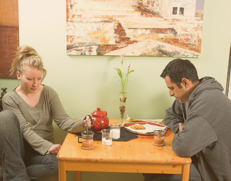 man and woman sitting at dinner table not talking