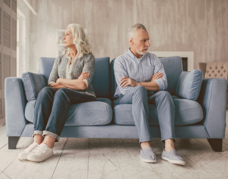 couple sitting on a couch not facing each other looking irritated