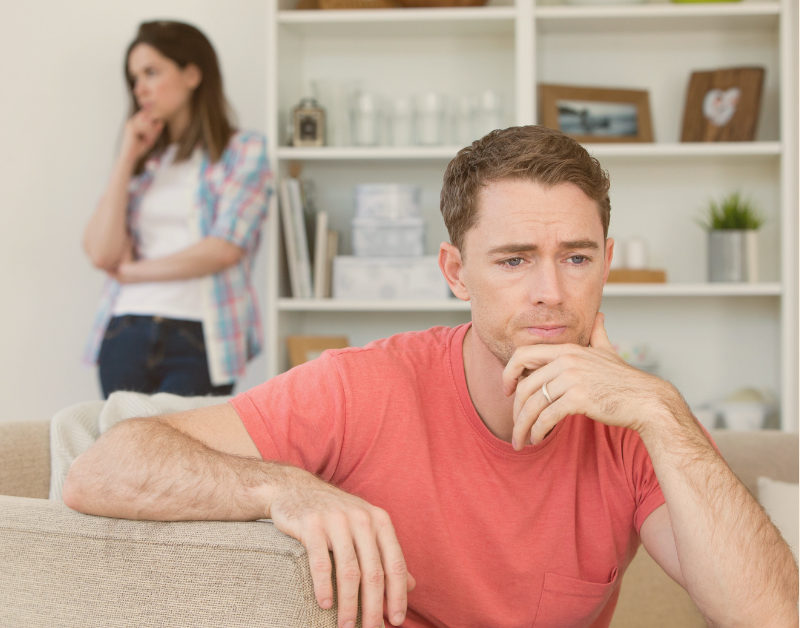 husband sitting on couch with wife walking behind him