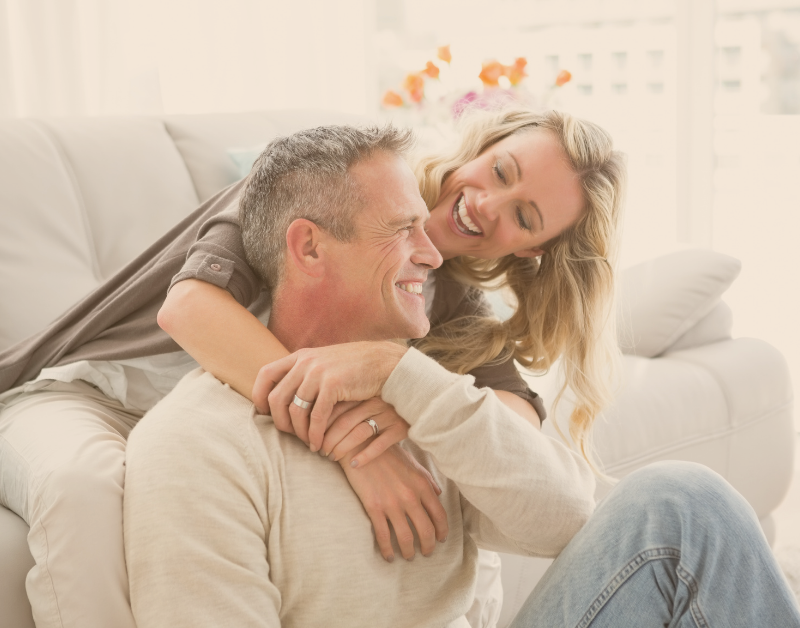 man and woman sitting on couch laughing and hugging